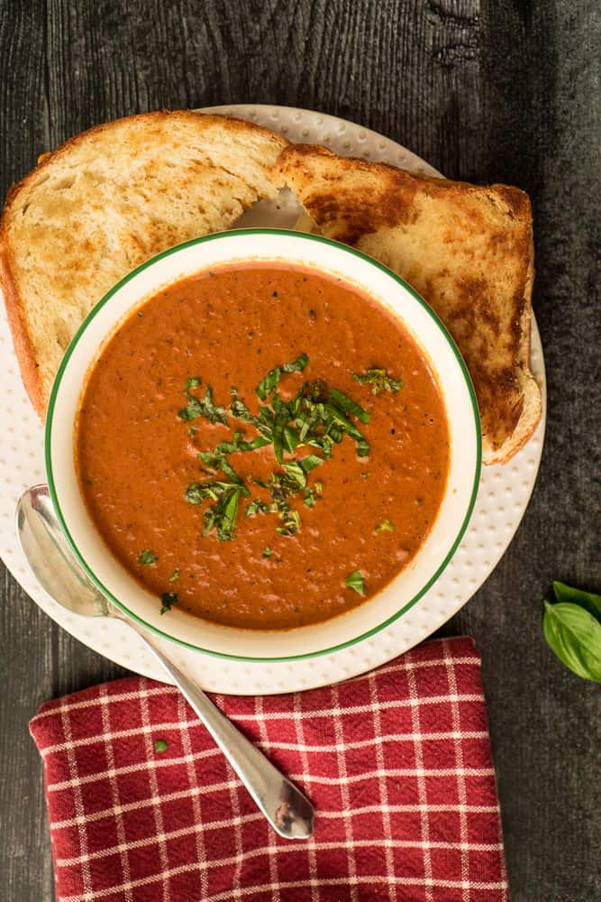creamy tomato soup on plate with grilled cheese and red checked towel