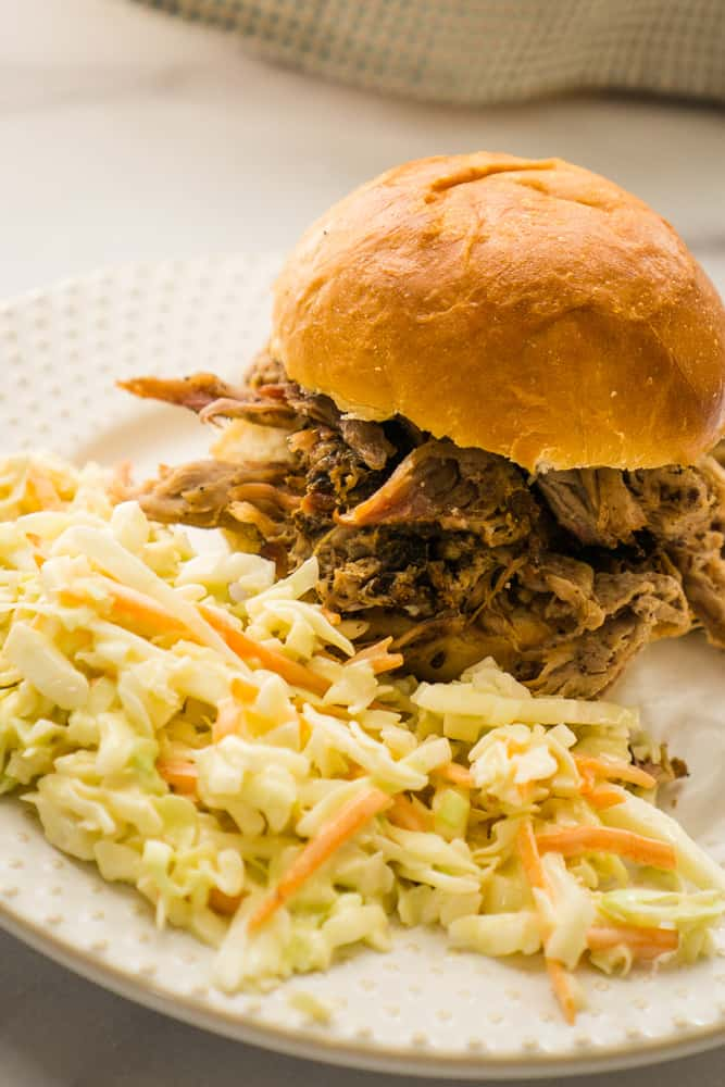 white plate with pulled pork sandwich and side of creamy coleslaw
