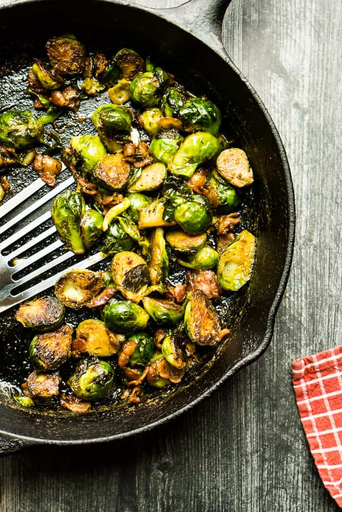 cast iron skillet with Brussels sprouts on wooden surface
