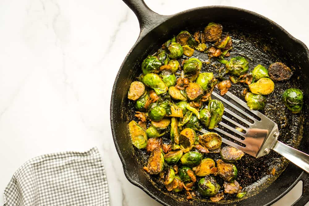 large skillet with caramelized Brussels sprouts about to be served
