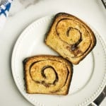 two slices cinnamon swirl sourdough bread, toasted and buttered, on white plate on marble counter