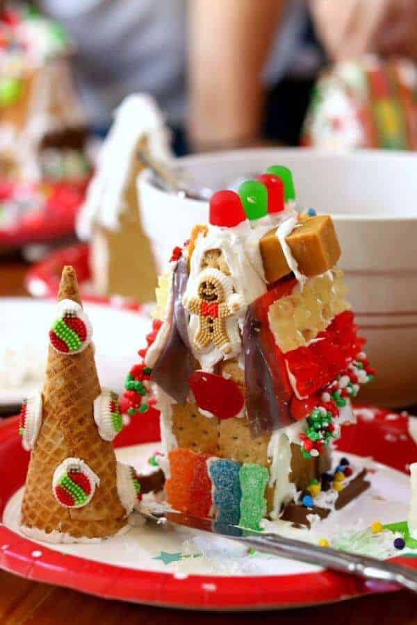 gingerbread house with gummy candies on red plate