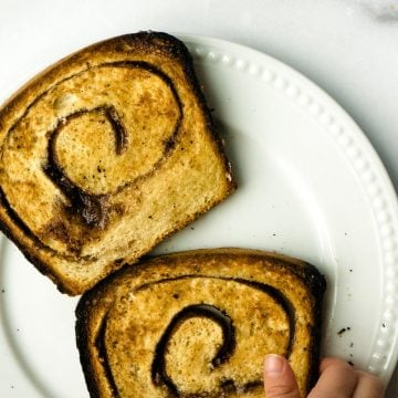 two slices toasted cinnamon sourdough bread, hand reaching for one