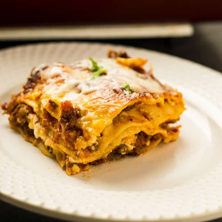 slice of lasagna on off white plate