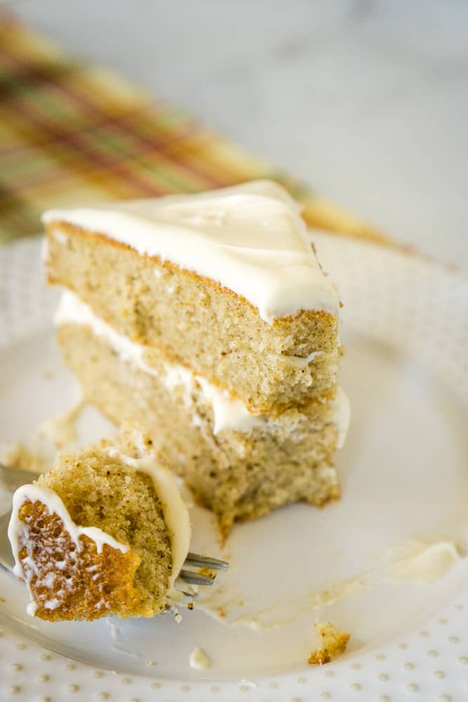 slice of layered spice cake with caramel cream cheese frosting on white plaid with fall plaid tablecloth in background