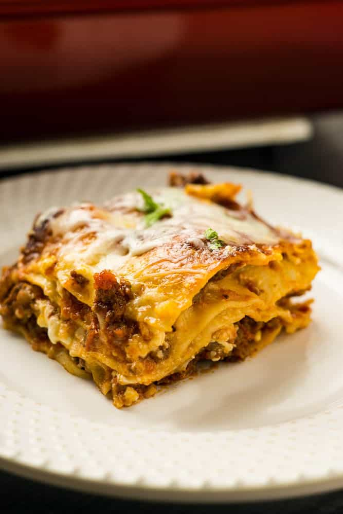 lasagna with layers of sausage and ricotta visible and red 9 x 13 pan in background