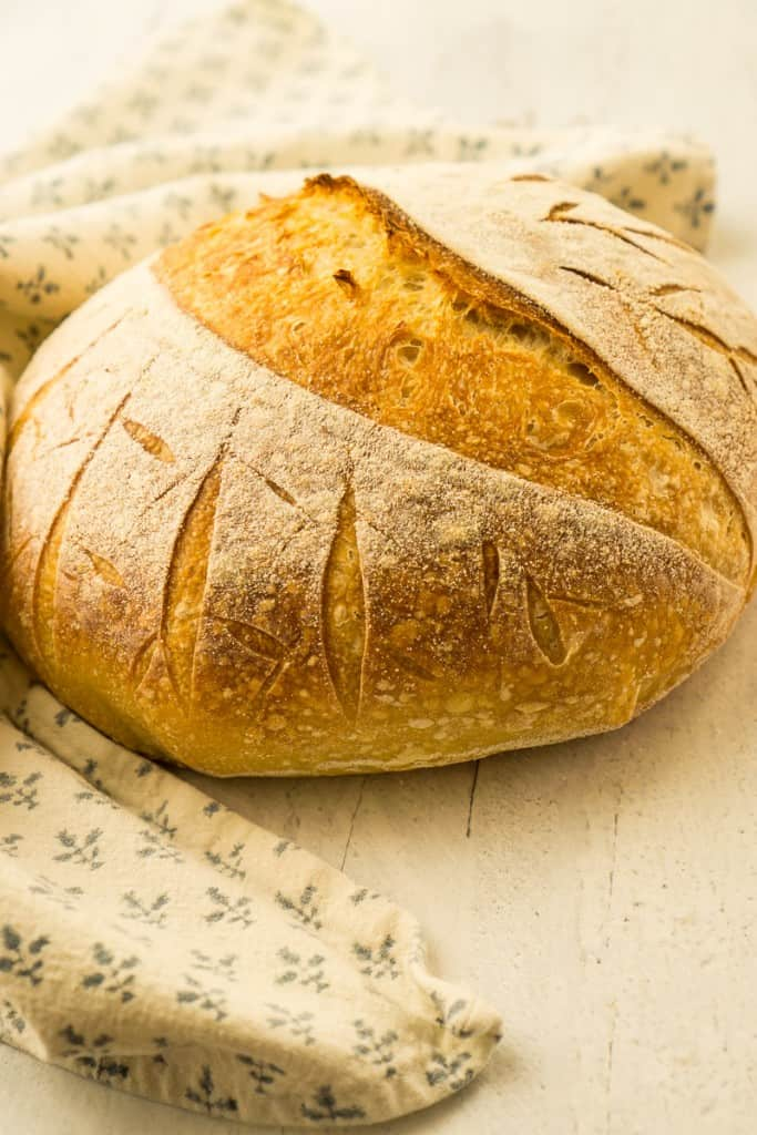 loaf of artisan sourdough bread on white wood surface
