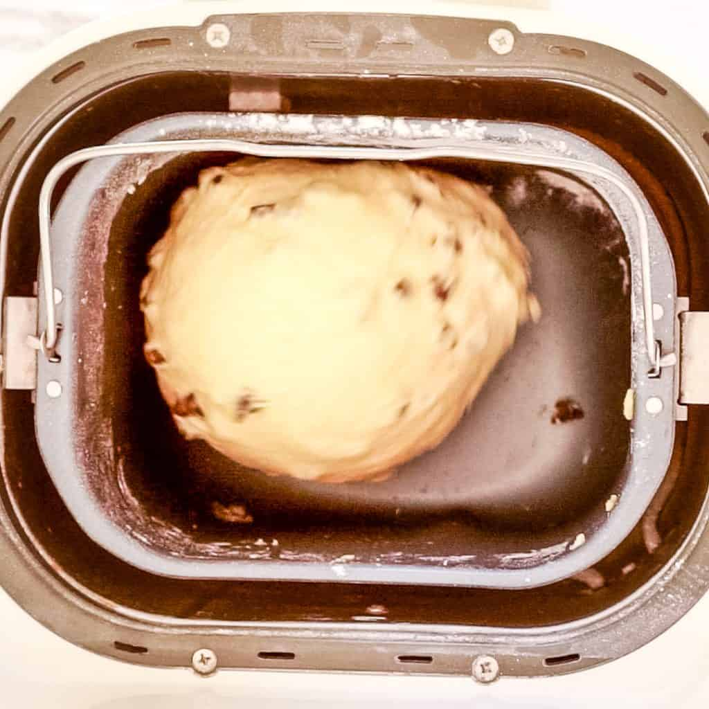 brioche dough in bread machine with chocolate chips being added