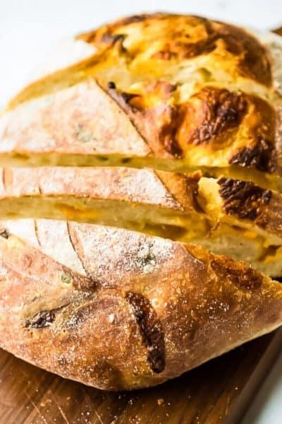 loaf of cheddar sourdough bread on cutting board
