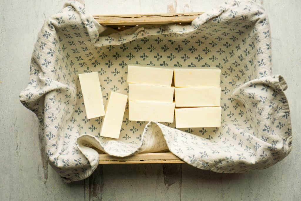 cleaning soap in white and blue tea towel lined basket