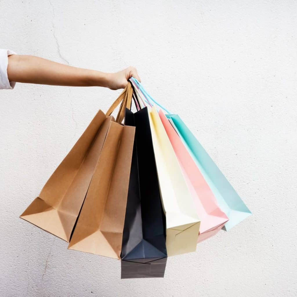 hand holding four shopping bags