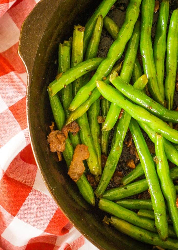 green beans in cast iron skillet, with cooked bacon