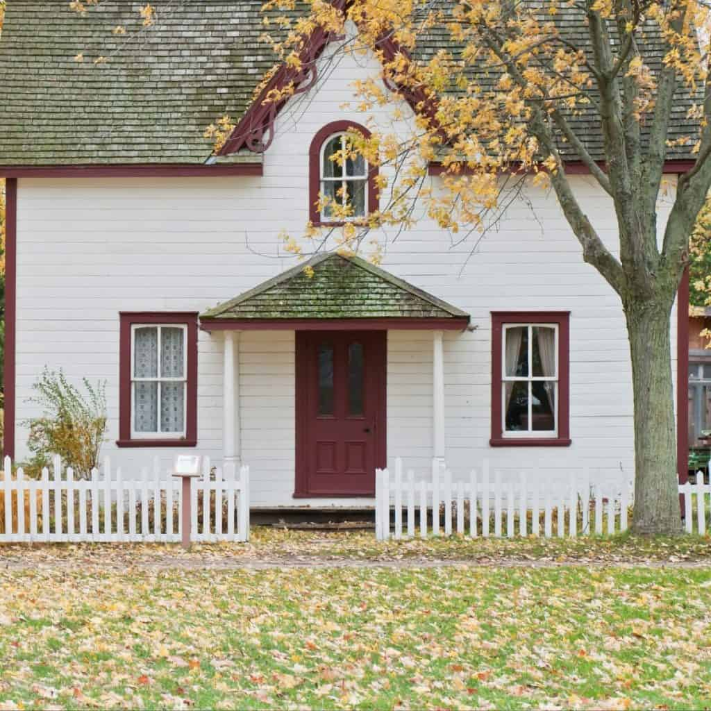white cottage with red trim with a tree in front