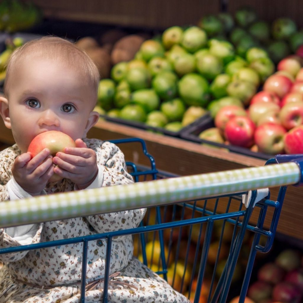 baby in grocery eating an apple