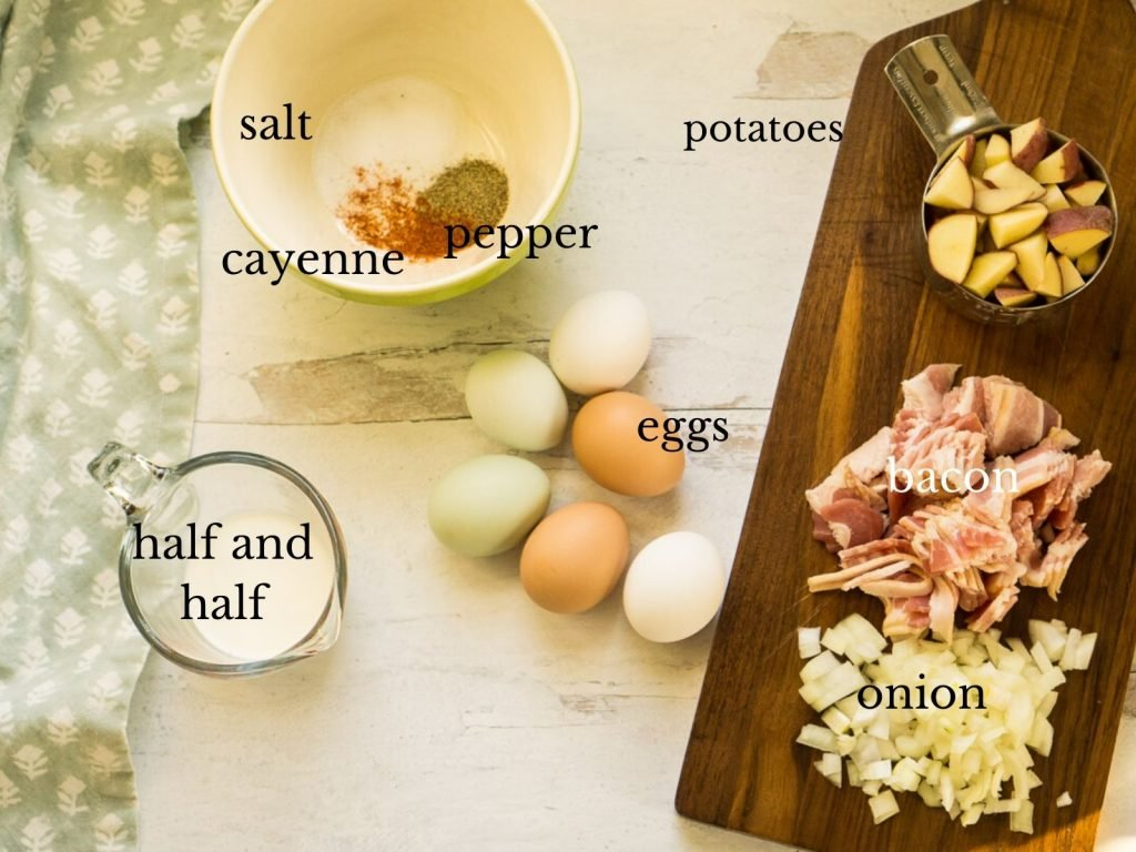 eggs, spices, potatoes, onion, bacon, and half and half laid out on counter