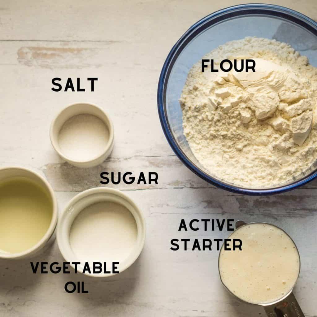 flour, salt, sugar, oil, and sourdough starter in bowls