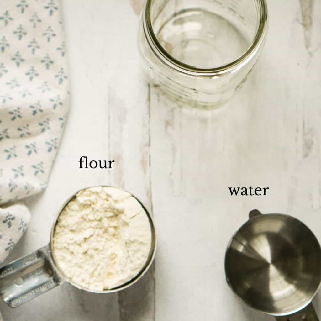 mason jar, flour, and water in measuring cups on white surface