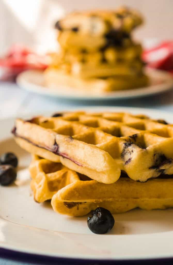 two waffles on plate, larger stack in background