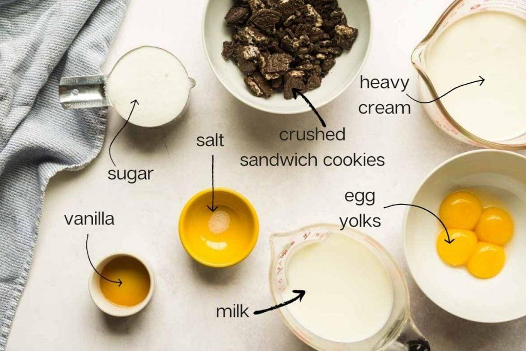 cream, milk, sandwich cookies, sugar, vanilla, and egg  yolks in bowls on concrete surface