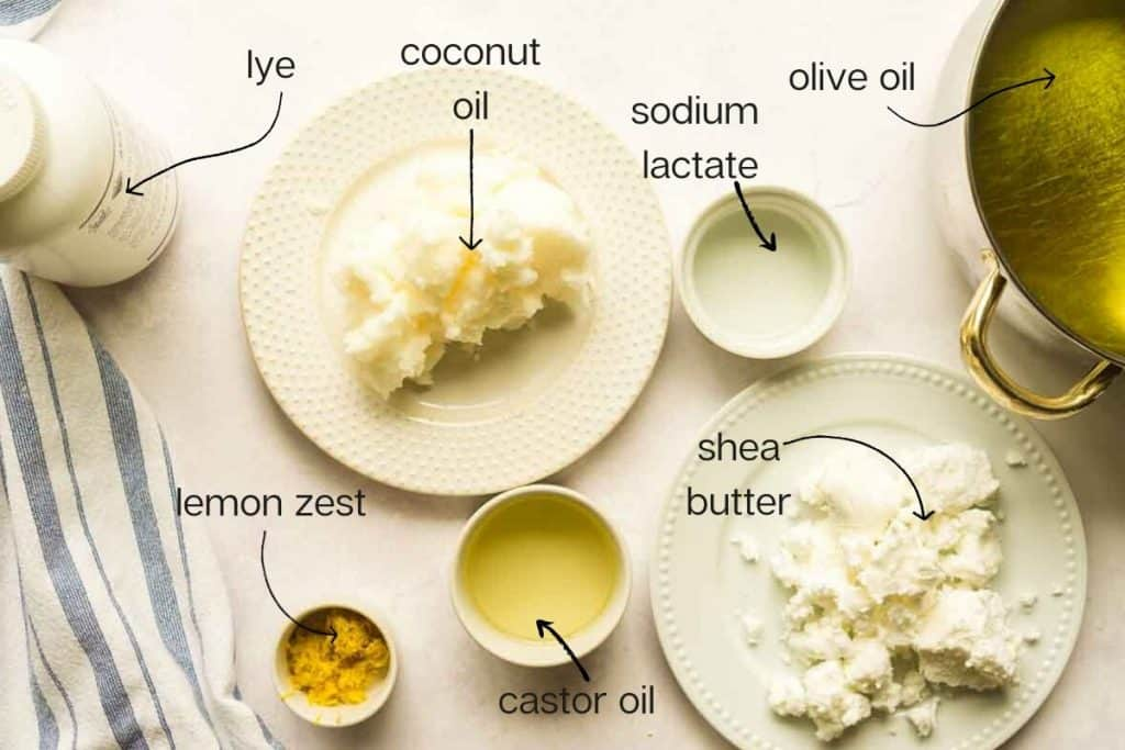 ingredients on concrete surface: coconut oil, olive oil, lemon zest, lye, and castor oil