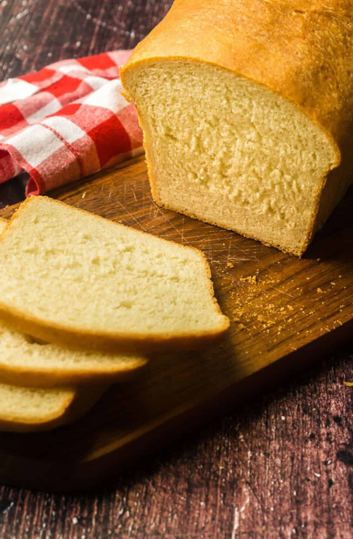 loaf of milk and honey sandwich bread being sliced on wooden board