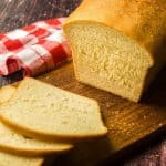 loaf of milk and honey sandwich bread on wooden cutting board