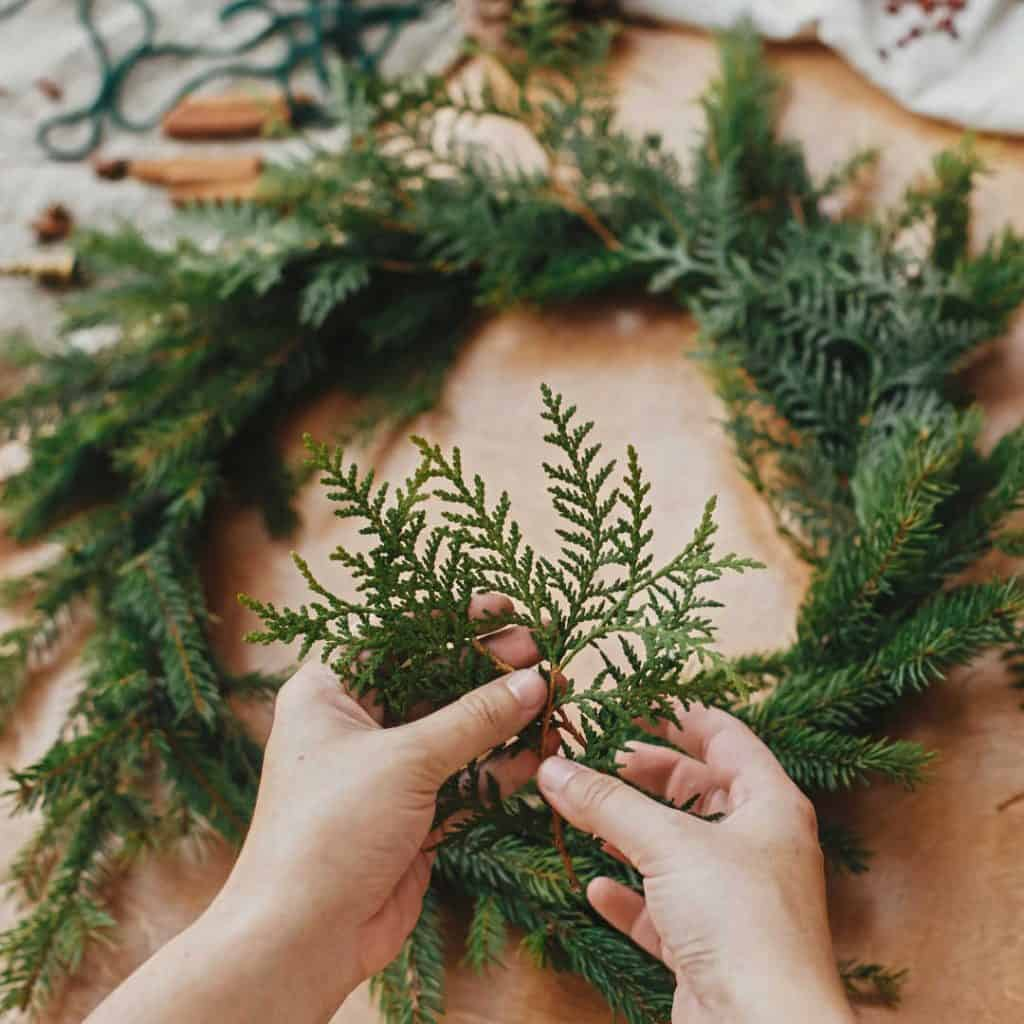 hands forming homemade wreath with natural greenery