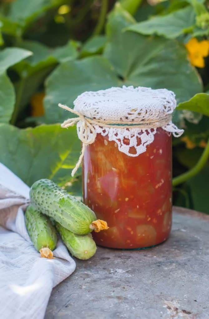 home canned food next to pickling cucumbers in garden