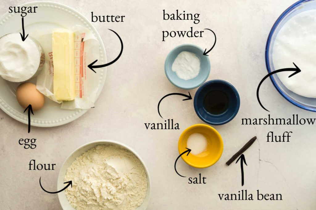 white surface with butter, sugar, egg, flour, vanilla, and other baking ingredients