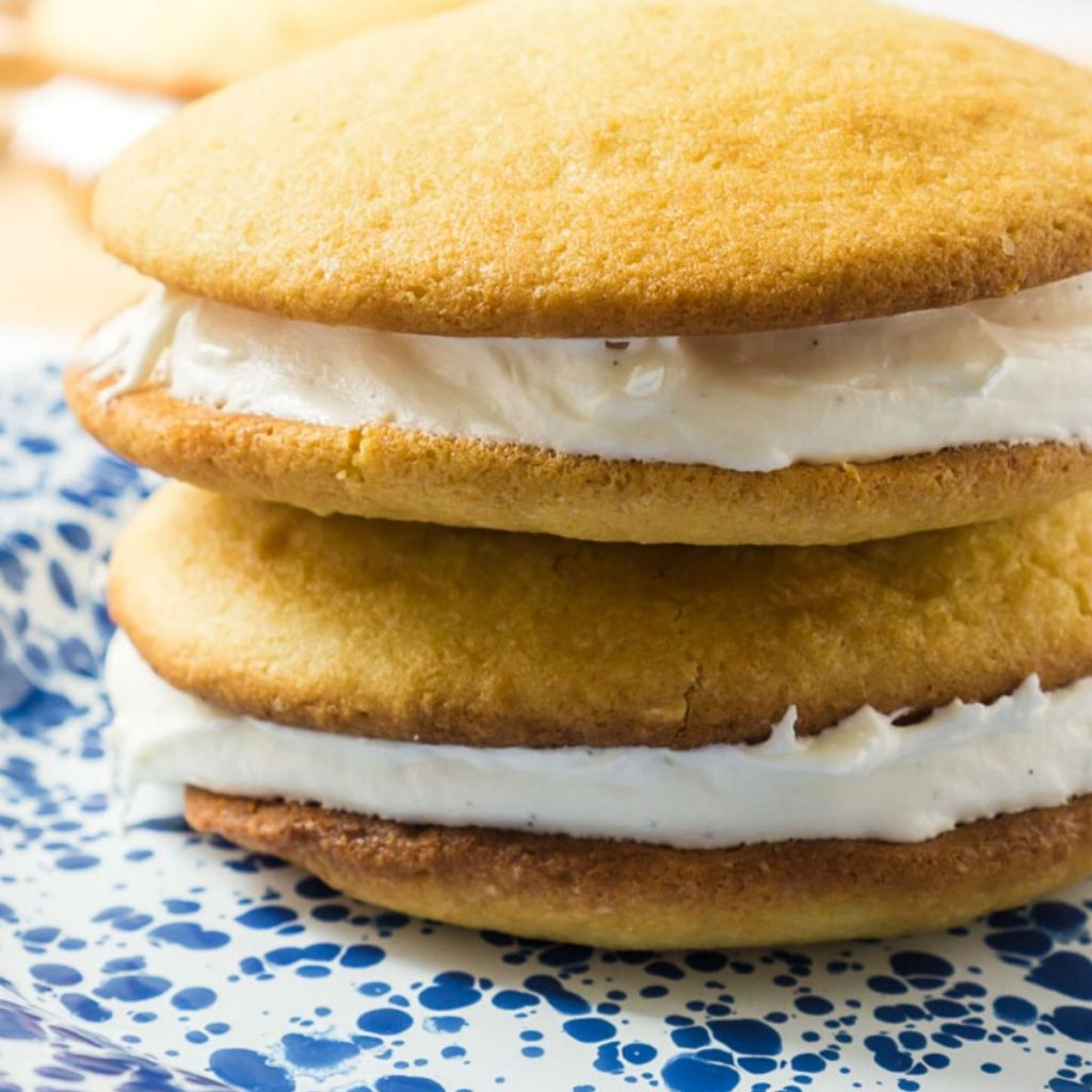2 vanilla Whoopie Pies with cream filling on plate