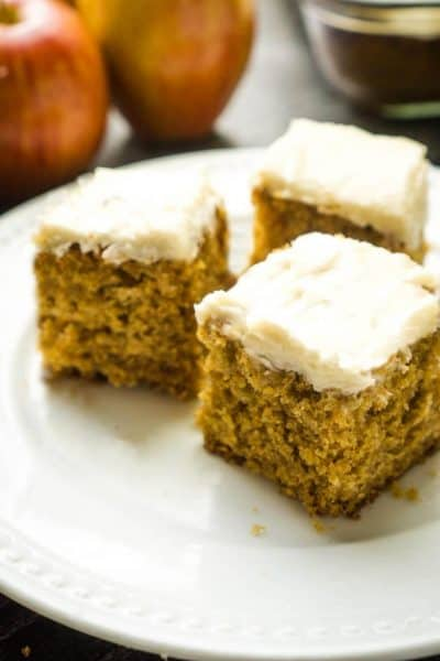 3 squares of apple cake with cream cheese frosting on white plate