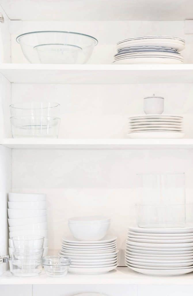 white plates and bowls organized in white cabinet