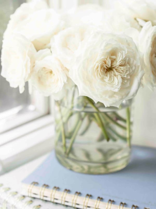 2 planners stacked with vase of flowers