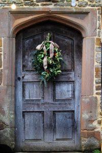 old door with fresh christmas greenery