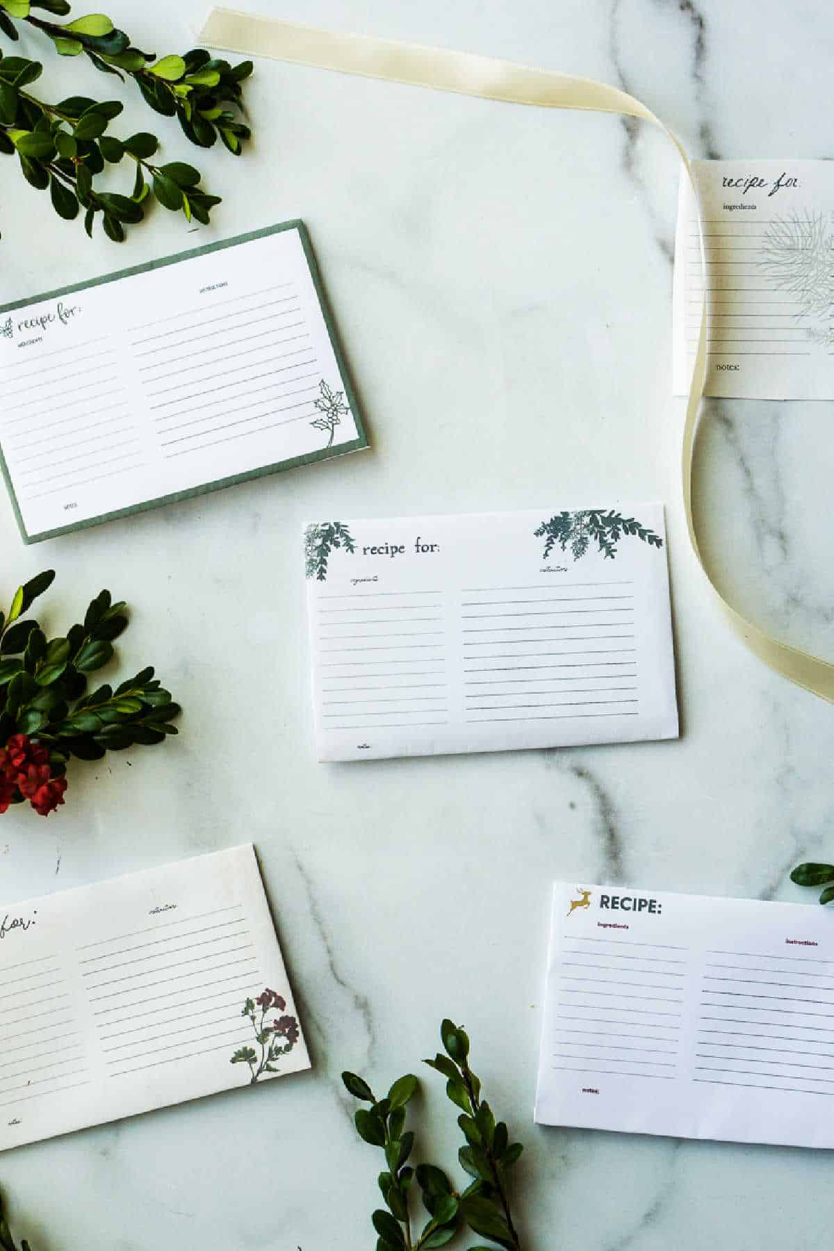 5 recipe cards on marble surface with greenery