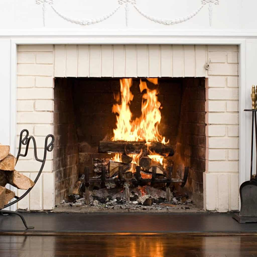 white fireplace and iron accessories