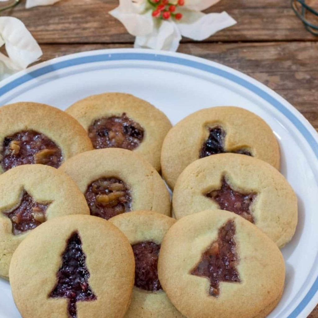 plate of jam filled cutout cookies with holiday designs