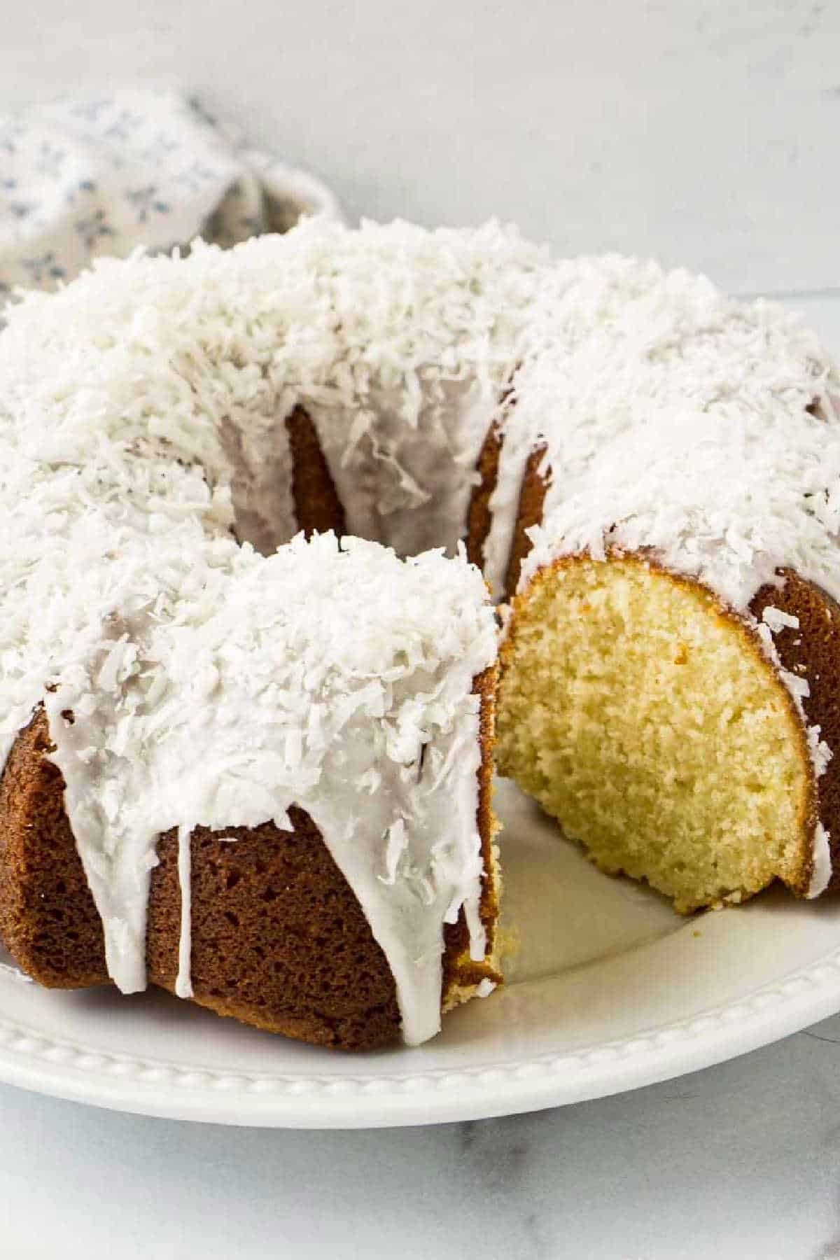 Bundt Cake with slice cut out and topped with flaked coconut