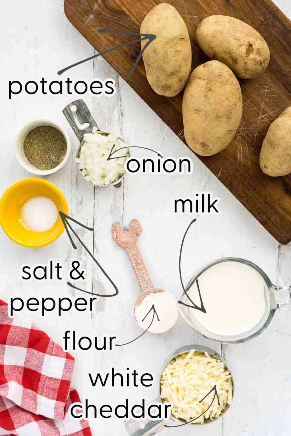 potatoes, milk, white cheddar, onion, salt, pepper, and flour on wooden surface