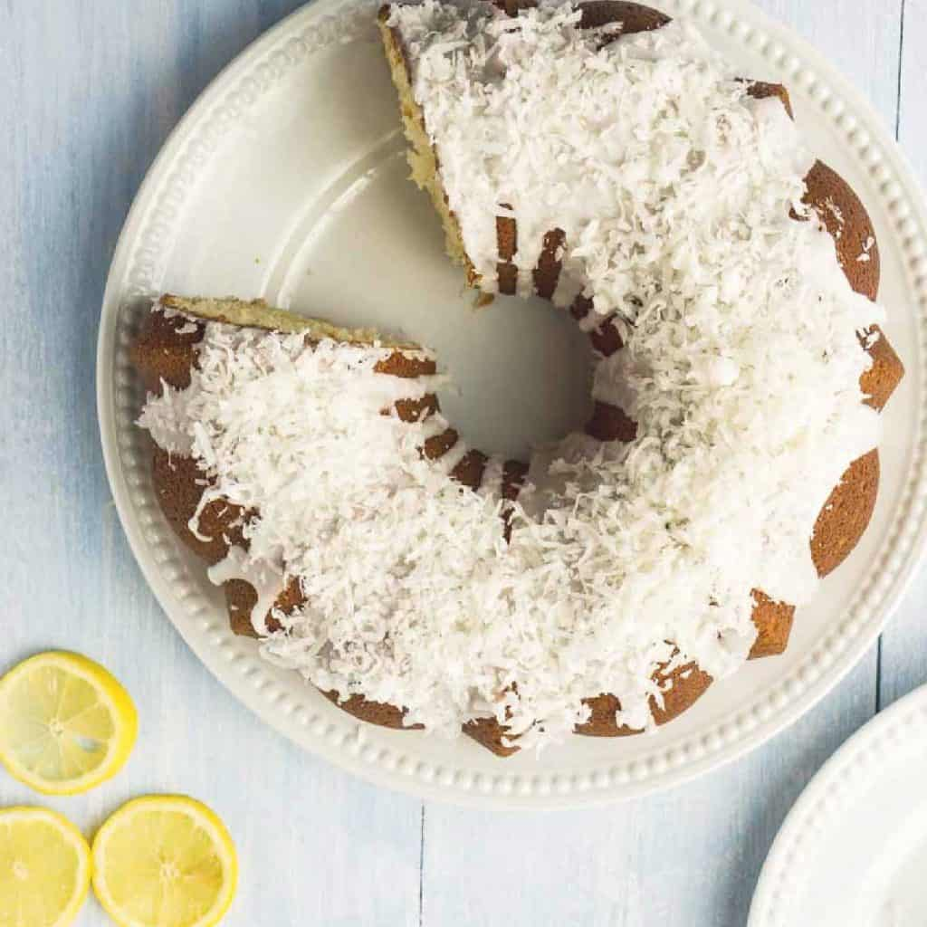 Bundt Cake topped with flaked coconut with slice missing