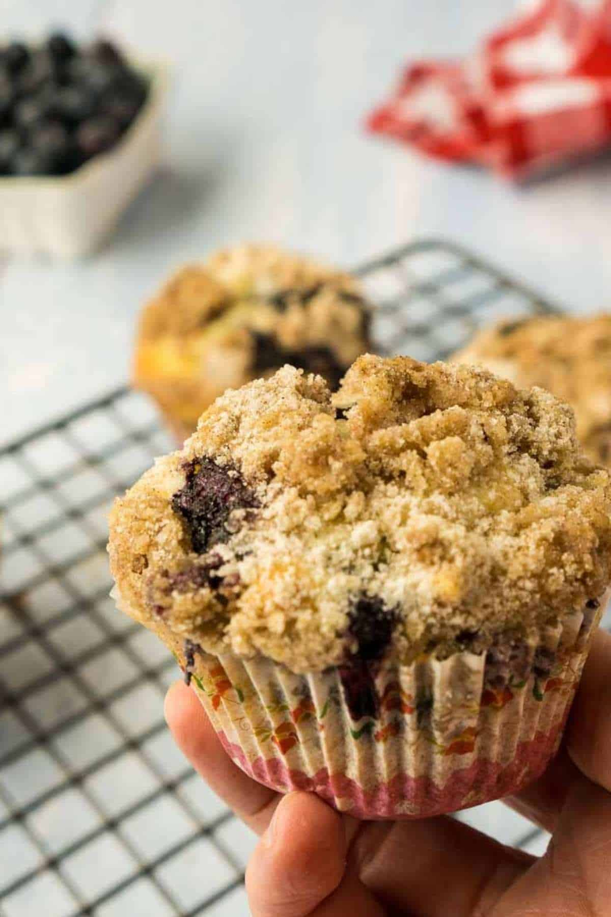 hand holding sourdough blueberry muffin with crumb topping