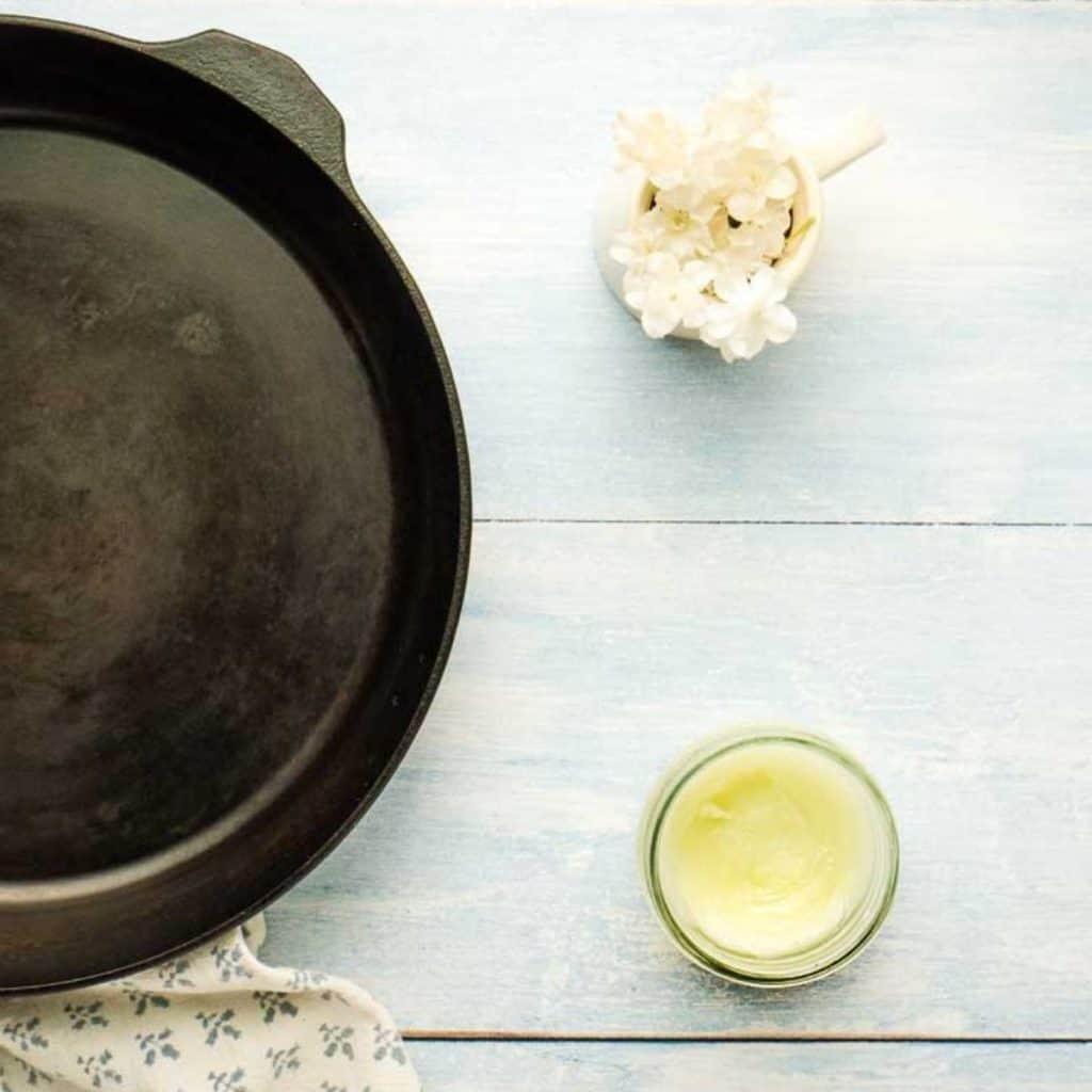 cast iron skillet with mason jar of homemade seasoning oil
