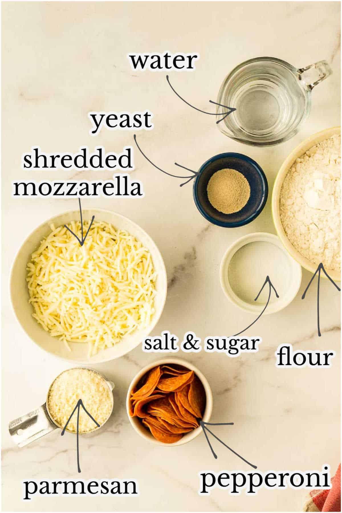 flour, salt, yeast, pepperoni, mozzarella, and parmesan on marble counter