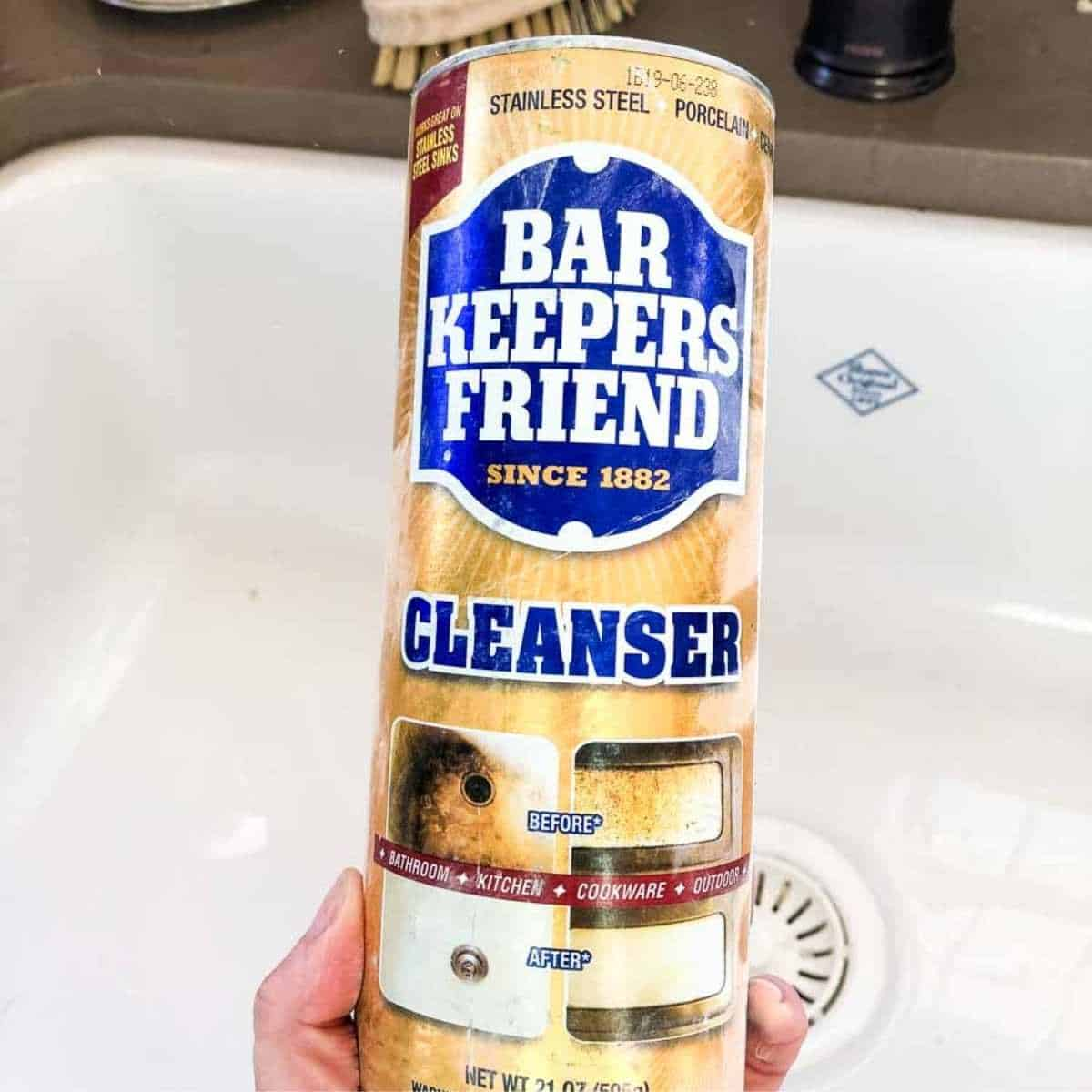 hand holding bar keepers friend container, white sink in background