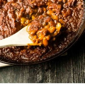 close up of scoop of baked beans in skiller