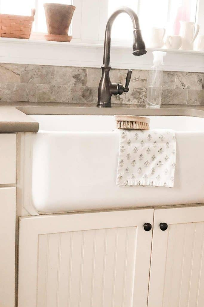 white fireclay sink with cream cabinets