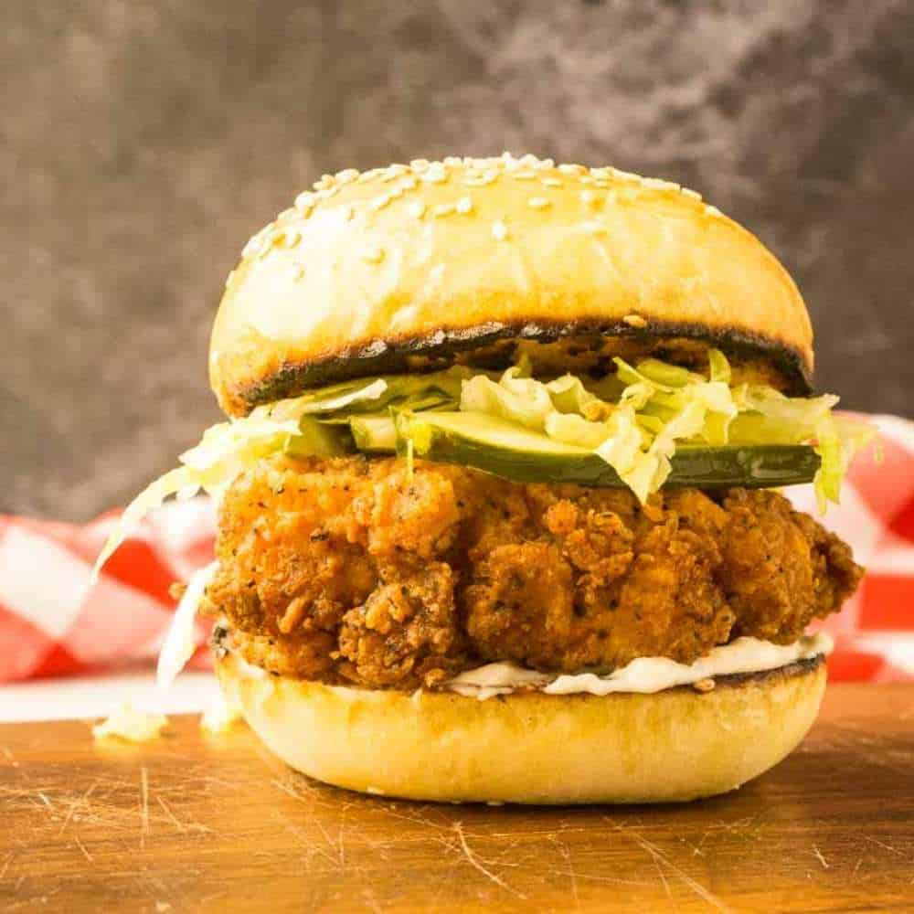 chicken sandwich with red and white checked napkin