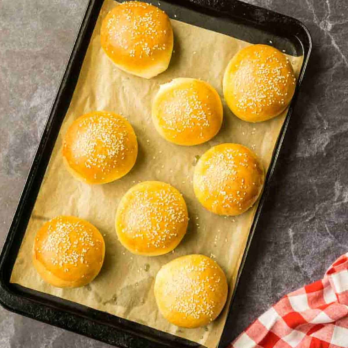 homemade burger buns on parchment lined baking sheet