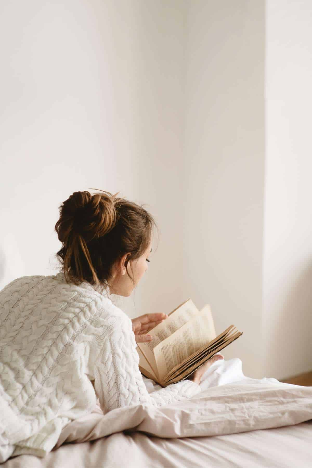 woman reading on bed looking away from camera