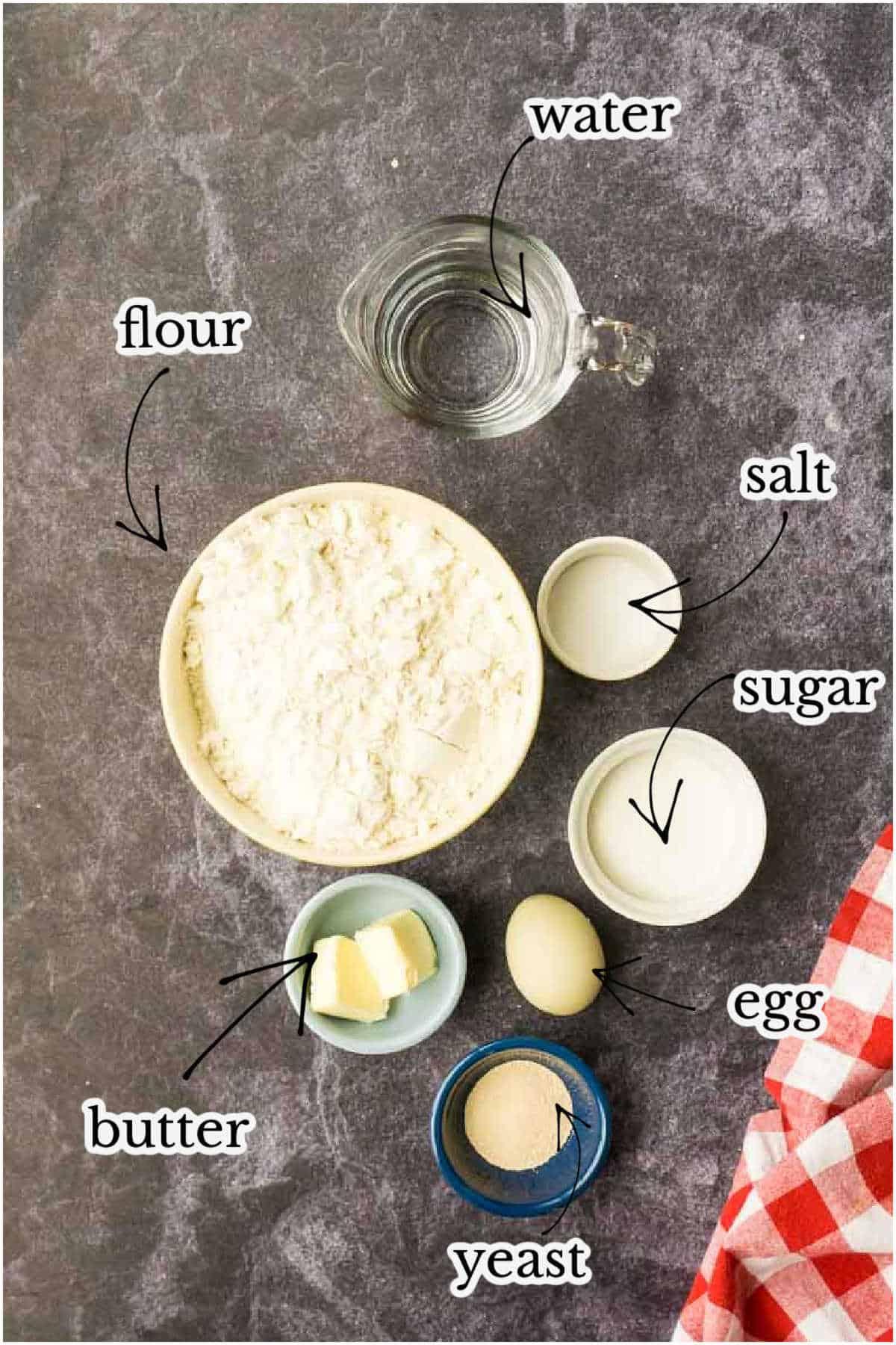 flour, butter, egg, sugar, salt, yeast in bowls on black counter